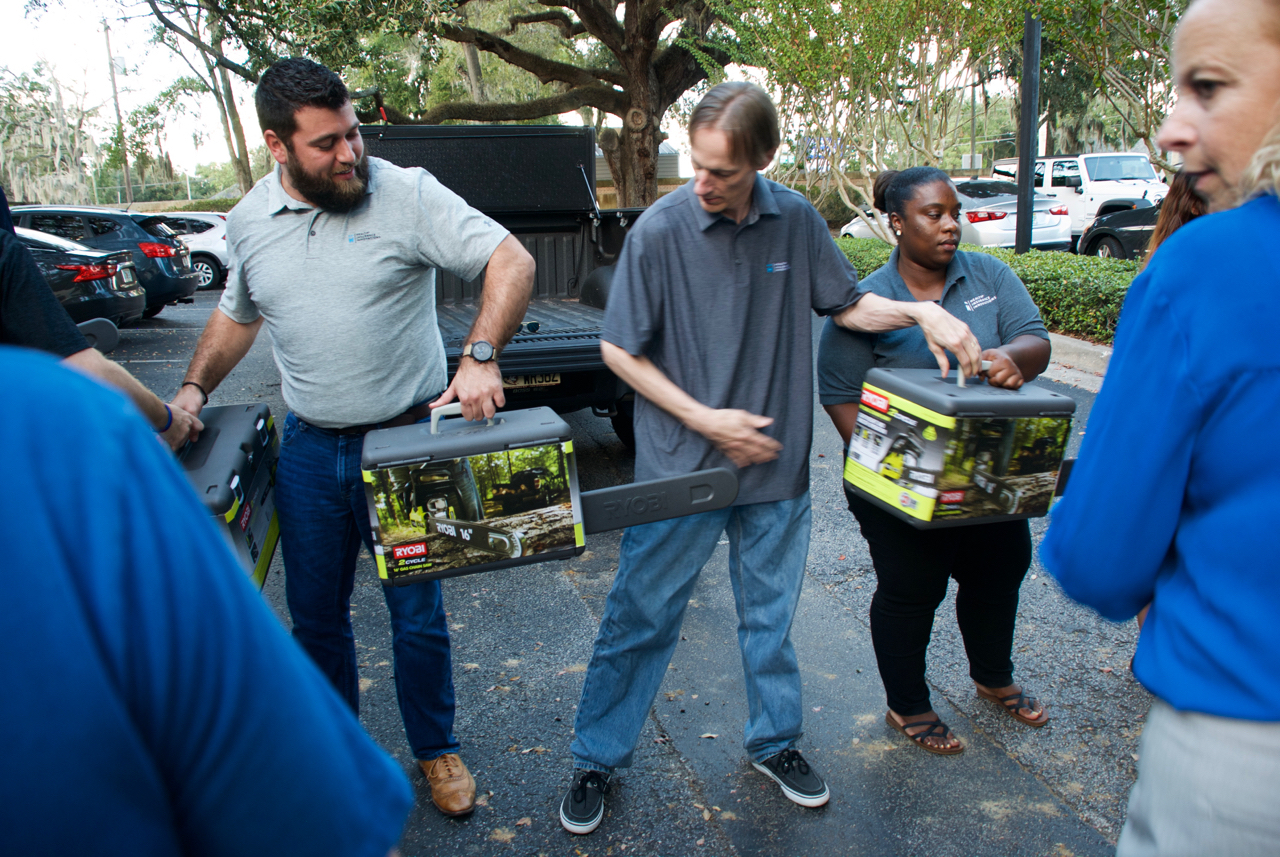 Health Insurance Innovations employees passing chainsaws to the supply truck for victims of Hurricane Michael